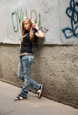 The girl - teenager on a background of a wall Stock Photo - 1438796
