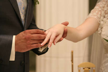 Hands of the groom and the bride during wedding ceremony photo