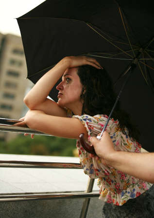 The lonely crying girl. The man covers from a rain a umbrella Stock Photo - 1489848