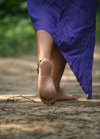 sunburnt: The girl with barefooted legs goes on a forest
