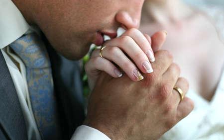 Der Bräutigam küsst die Hand der Braut  Standard-Bild
