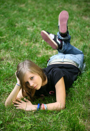 The girl - teenager lays in a grass. Stock Photo - 1590812