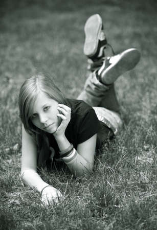 The girl - teenager lays in a grass. Stock Photo - 1598397