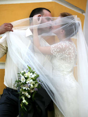 debutante: The groom and the bride kiss having closed by a veil