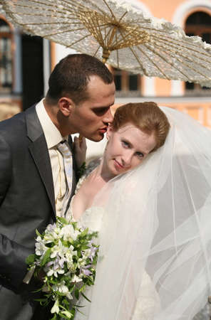 The groom and the bride kiss in park photo