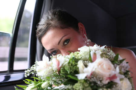contestant: Beautiful the bride with a bouquet in the automobile Stock Photo