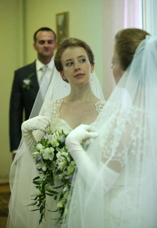 fiance: The beautiful young bride and the groom are reflected in a mirror