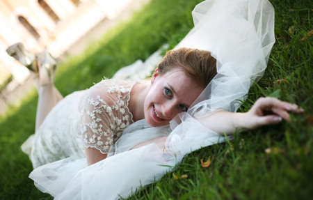 debutante: The beautiful bride with a wedding bouquet lays on a grass