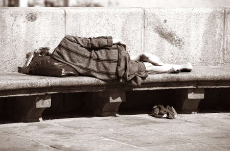 drunkenness: A homeless woman sleeping on a park bench