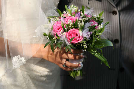 Bouquet of flowers on a background of a dress of the bride and a suit the groom Stock Photo - 1772007