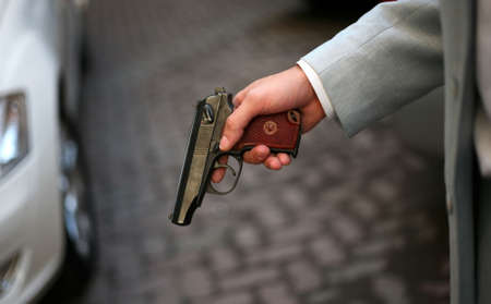 character assassination: The person in a grey suit with a pistol