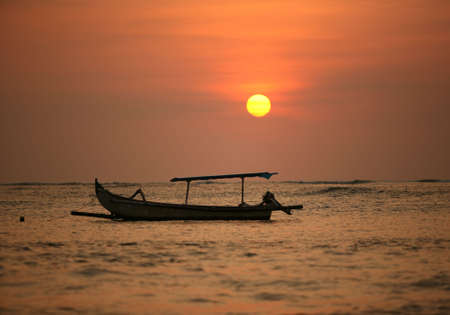 Drifting boat on a sunset. Coast of the Indian ocean. Bali Stock Photo - 2028903