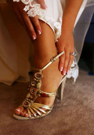 garter: Wedding shoes on barefooted legs of the bride Stock Photo