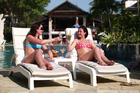 Two young girls with cocktails near the swimming pool Stock Photo - 2105673