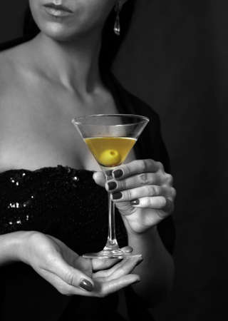 The image of a glass from martinis in a female hand on a black background