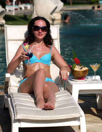 Young girs with cocktails near the swimming pool photo