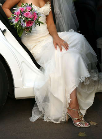 The bride with a bouquet leaves the car