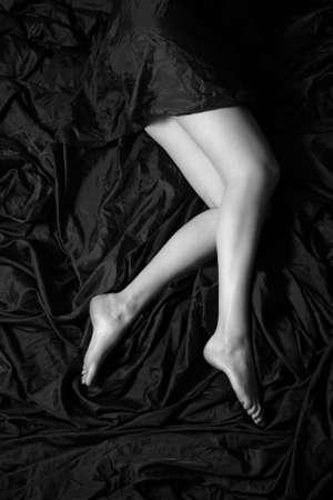 Beautiful legs of the woman on a silk fabric photo