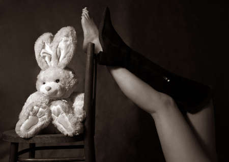 Beautiful legs of the woman and a toy hare photo