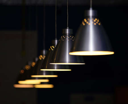 ambient light: Many metal lamps at dark restaurant
