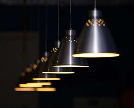 Many metal lamps at dark restaurant