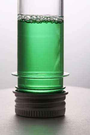 aseptic: Test tube with a green liquid on a white background