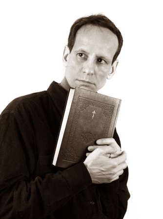 vicar: Thoughtful the man with the bible on a light background