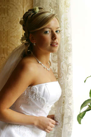 The beautiful bride at a window. Natural illumination Stock Photo - 2490114