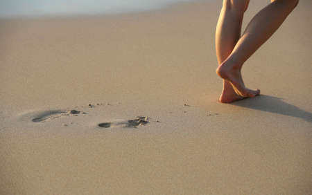 Image of foot prints and legs on beach