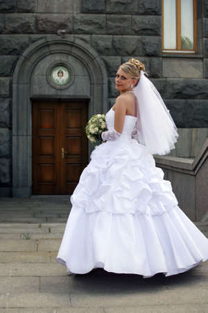 The beautiful bride with a bouquet on a background of church photo