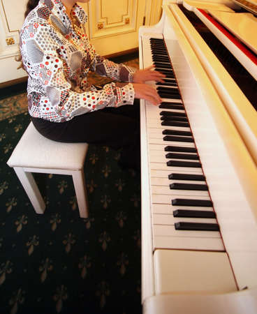 Woman playing the white piano in an interior photo