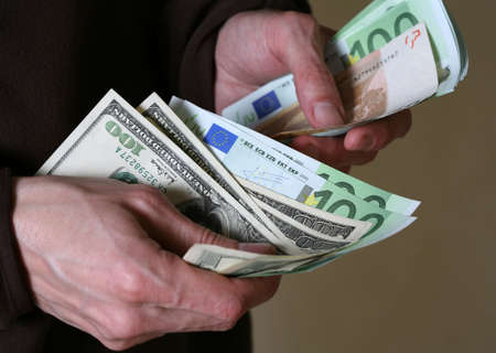 Man's hands hold Euro and dollars banknotes money Stock Photo - 2846067