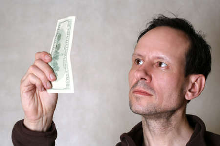 authenticity: The adult the man checks dollars on authenticity Stock Photo