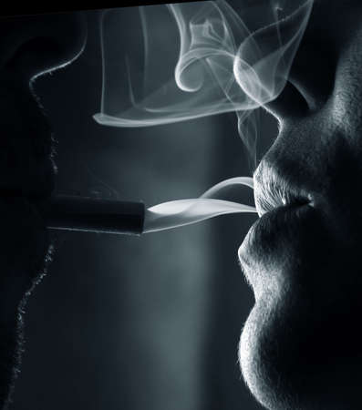 plant drug: Two silhouettes of smoking people close-up Stock Photo