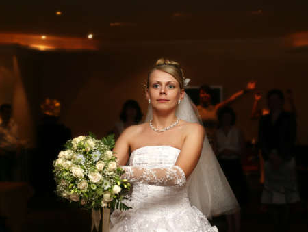 The bride throws a wedding bouquet to the girlfriends photo