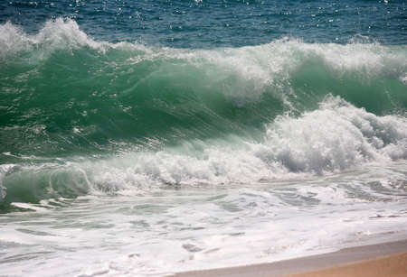Big wave crashes on to the shore photo