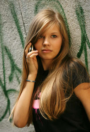 graphity: The young girl with phone on a background of a wall with graffiti