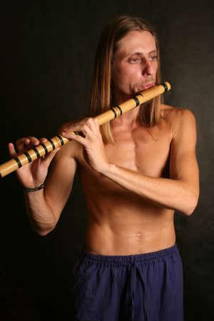 musicality: Un uomo che giocano il suo strumento a fiato con espressione Archivio Fotografico