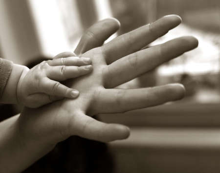 mom and dad: The image of hands of parents and the kid. bw+sepia