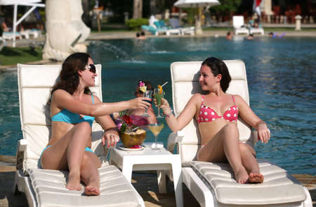 Two young girls with cocktails near the swimming pool photo