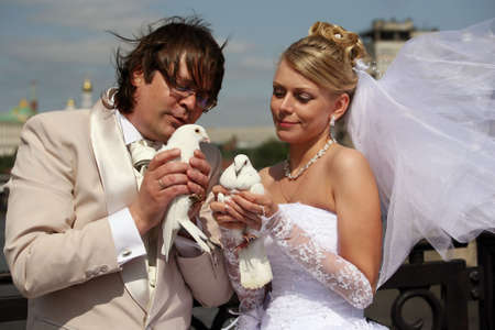 The groom and the bride with white pigeons photo