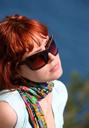 The woman with red hair enjoys the sun photo