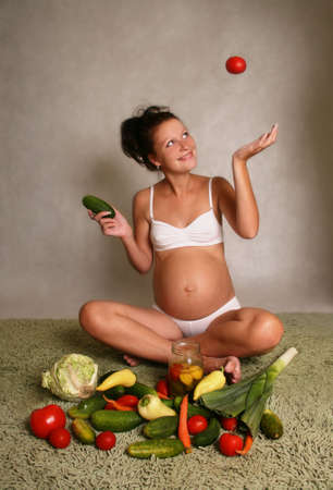 The pregnant woman on a background of various vegetables Stock Photo - 3294895