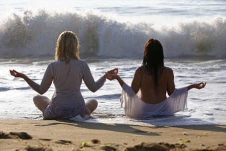 The blonde and brunette meditate on a beach