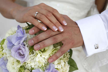 Hand of the groom and the bride with wedding bouquet photo