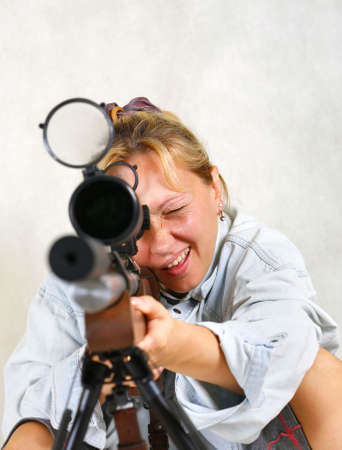 The girl with a gun in studio photo