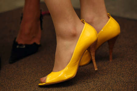 Legs of the girl in yellow shoes photo