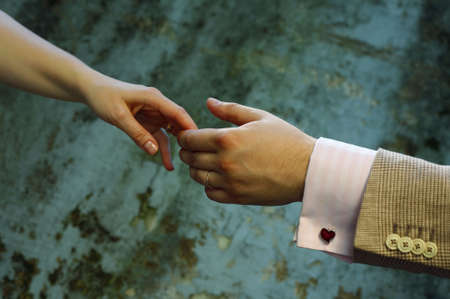 agrees: Female hands in mans hands on old wall background