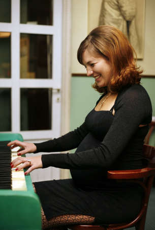 The pregnant woman plays on the piano
