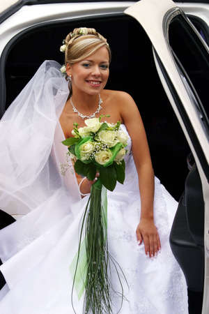 The beautiful bride with a bouquet in the automobile